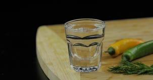 Alkoholvodka i skjutit exponeringsglas på skärbräda med varm peppar arkivfoto