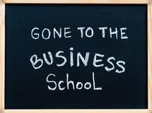 Allé au message d'école de commerce écrit avec la craie blanche sur le tableau noir de cadre en bois images libres de droits