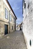 Allée étroite typique pavée avec des pavés ronds et avec de vieilles maisons en pierre au centre de la vieille ville de Guimaraes Image stock