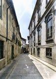 Allée étroite typique pavée avec des pavés ronds et avec de vieilles maisons en pierre au centre de la vieille ville de Guimaraes Image libre de droits