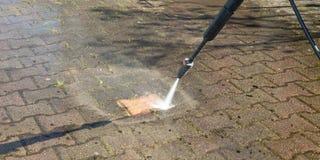Allée de nettoyage de travailleur extérieur de plancher avec un jet d'eau de pression photos stock