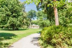 Allée de parc avec le pavillon sur le fond Image stock