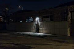Allée effrayante foncée la nuit avec l'entrée à déchenchements périodiques d'entrepôt de porte Images stock