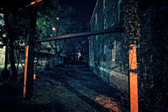 Allée foncée effrayante de ville à côté d'un parking urbain vide et d'un v Photo stock