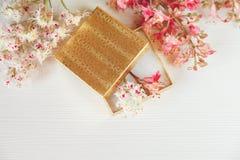 Allí la caja abierta del oro con las ramas blancas y rosadas del árbol de castaña está en la tabla blanca, visión superior entona Imagenes de archivo