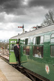 All aboard!. SHEFFIELD PARK, UK - MARCH 19, 2016: Guard on train prepares to blow his whistle on the Bluebell Line Stock Images
