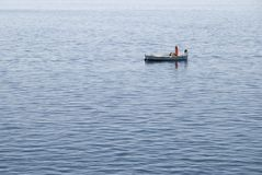 All Alone. A fisherman alone at sea Royalty Free Stock Photos