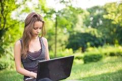 All'aperto con il suo computer portatile. Immagini Stock