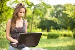 All'aperto con il suo computer portatile. Fotografia Stock