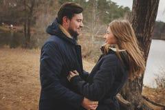 All'aperto felici delle giovani coppie amorose su accogliente riscaldano insieme la passeggiata nella foresta di autunno immagini stock