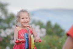 All'aperto feste della ragazza del bambino che oscillano sull'attrezzatura di legno del campo da giuoco fotografia stock