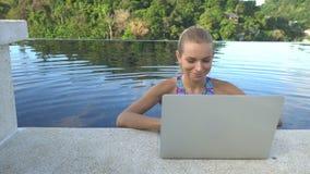 All'aperto ritratto della donna felice bionda graziosa in bikini con il computer portatile in una piscina di infinito del tetto video d archivio