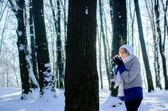 All'aperto ritratto della giovane donna graziosa con neve in sue mani all'aperto su cielo blu e sul fondo gelido degli alberi Fotografie Stock Libere da Diritti