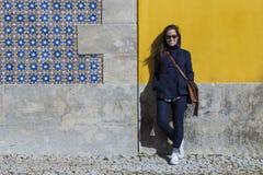 All'aperto ritratto di giovane bella donna sopra le sedere gialle della parete Immagine Stock