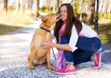 All'aperto ritratto di stile di vita di bella ragazza con un cane sveglio sopra fotografia stock