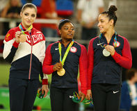 All-around gymnastics medalists at Rio 2016 Olympics Aliya Mustafina of Russia (L),Simone Biles and Aly Raisman of USA stock images
