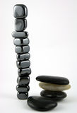 All in the Balance. 11 Smaller stones in balancing perfectly next to 4 larger stones not in balance Royalty Free Stock Images