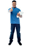 All the best for your exams!. Student holding books and showing thumps up sign to camera Stock Photo