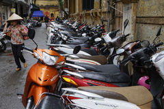 All bikes in a row. HANOI, VIETNAM, October 31, 2016 : Lots of motorbike parked along a narrow street of Hanoi. Transportation of persons in Hanoi is mainly made Stock Photography