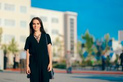 Woman Wearing Elegant Romper and Statement Necklace at Outdoor Event. All black dress code outdoor party guest arriving to dinner Stock Images