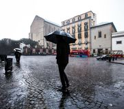 Man is walking with umbrella during heavy rain in the town stock image