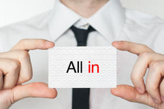 All in. Businessman holding business card. All in. Businessman in white shirt with a black tie showing or holding business card Royalty Free Stock Image