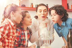 All children and their teacher looking at the reaction. Blow here. Attractive women raising her eyebrows while doing experiment and waiting for result Royalty Free Stock Photos