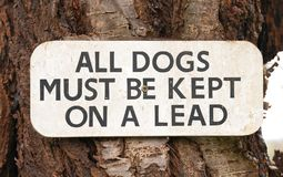 All Dogs Must Be Kept On Lead sign - sign on tree. All Dogs Must Be Kept On Lead sign royalty free stock image