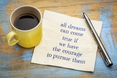 All dreams can come true if you have courage ... All dreams can come true if you have courage to pursue them - handwriting on a napkin with a cup of espresso stock photography