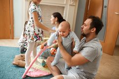 All family father, mother, two daughters and little baby son spending time on the carpet in the room stock photos