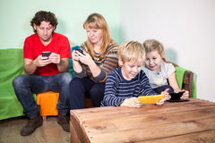 All family having fun with games on smartphones Royalty Free Stock Photography