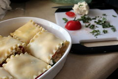 All the fixings. Caprese lasagna rolled waiting for the sauce with cut roma tomato mozzarella and basil on chopping board Royalty Free Stock Photos