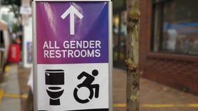 All Gender Restroom Sign at a Gay Pride Festival. An all gender restroom sign on a city sidewalk at a gay pride festival stock video footage