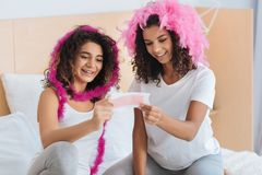 Joyful sisters pretending to have beauty salon at home. All the girly stuff. Waist up shot of a radiant siblings grinning broadly while trying on pink feather Stock Image