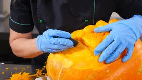 All Hallows Day preparing. Closeup shot of hands in gloves carving from a pumpkin Jack-o. Cutting Scary glowing. Halloween pumpkin . Special knives. 4k stock footage