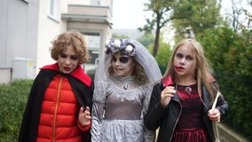 All Hallows Eve. Children in costumes and makeup of a dead bride and a vampire walk along the street celebrating. Halloween stock footage