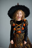 All Hallows Eve. Girl shows the evil sorceress. She is wearing a black-and-orange dress and hat. From under his hat sticking disheveled hair. The girl has an Stock Images