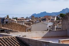All houses and roofs in brown tones. View of the roofs of an ancient, historic town house and the mountain beyond the city; all houses and roofs in brown tones stock images
