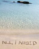 All I need message written on white sand, with tropical sea waves in background Royalty Free Stock Photos