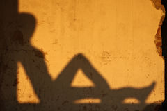 All I see is you. A woman's shadow reflects on a broken wall at sunset royalty free stock image