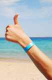 All inclusive. Hand with all inclusive bracelet over sea background Royalty Free Stock Photos