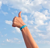 All inclusive. Hand with all inclusive bracelet over sky Royalty Free Stock Image