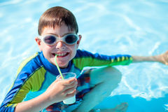 All inclusive vacation. Cute boy at all inclusive resort swimming pool sipping cocktail Stock Photography