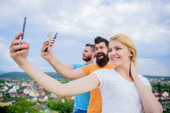 We are all individuals. People enjoy selfie shooting on nature. Best friends taking selfie with camera phone. girl. And men holding smartphones in hands royalty free stock image