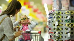 All'interno ritratto del bambino femminile felice con la sua abbastanza bella madre che sceglie gli occhiali da sole nel supermer archivi video
