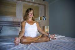 All'interno ritratto di bella e posa di pratica sana adatta di yoga della donna 30s a letto calma e di rilassato concentrato nell immagini stock libere da diritti