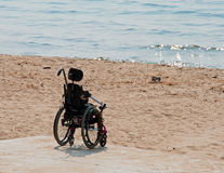 All the Kids Came to the Beach. A photograph of an empty wheelchair sitting on a beach Royalty Free Stock Photography
