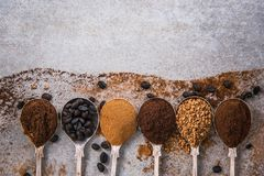All kind of coffee on spoons on concrete slate. Overhead view. Food background Stock Photo