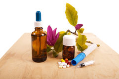 All kinds of medicines. All kind of medicines like pills, capsules,  fluid and a syringe on a wooden shelf with Magnolia flowers Royalty Free Stock Image