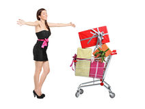 This is all for me?. An excited woman posing next to a shopping cart full of gifts  on white background Royalty Free Stock Image